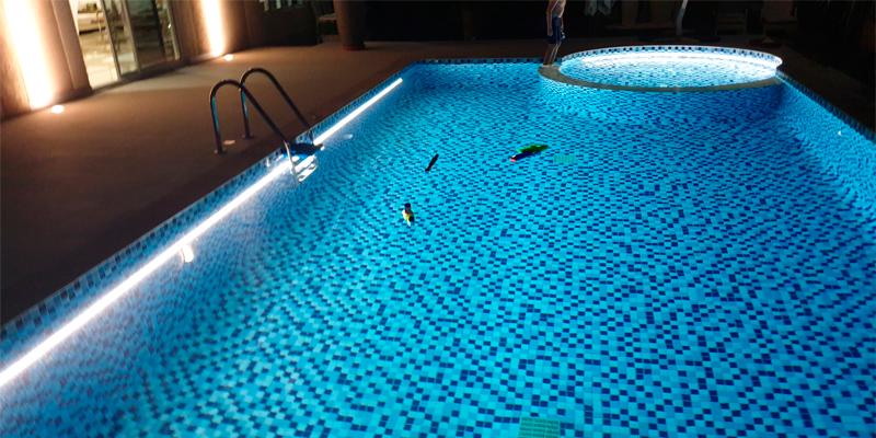 piscina con revestimiento gresite tonos azules e iluminación interior con tiras led